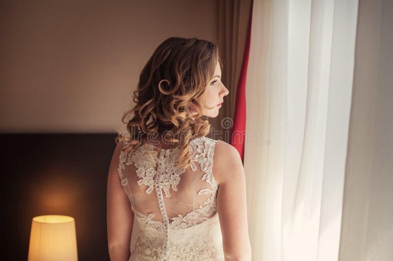 Красивая невеста стоя в ее спальне и смотря в окне стоковые фотографии rf