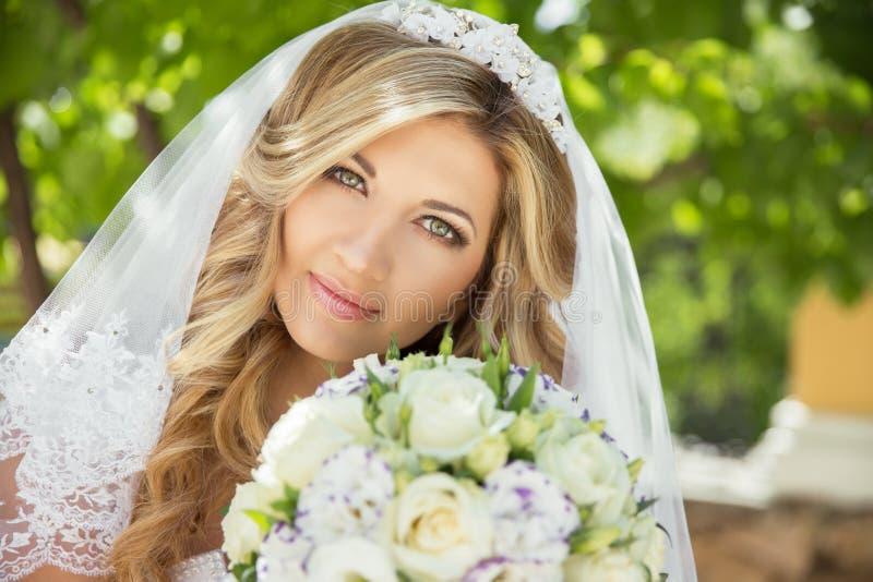 Красивая невеста с букетом свадьбы цветков outdoors в gree стоковое фото rf