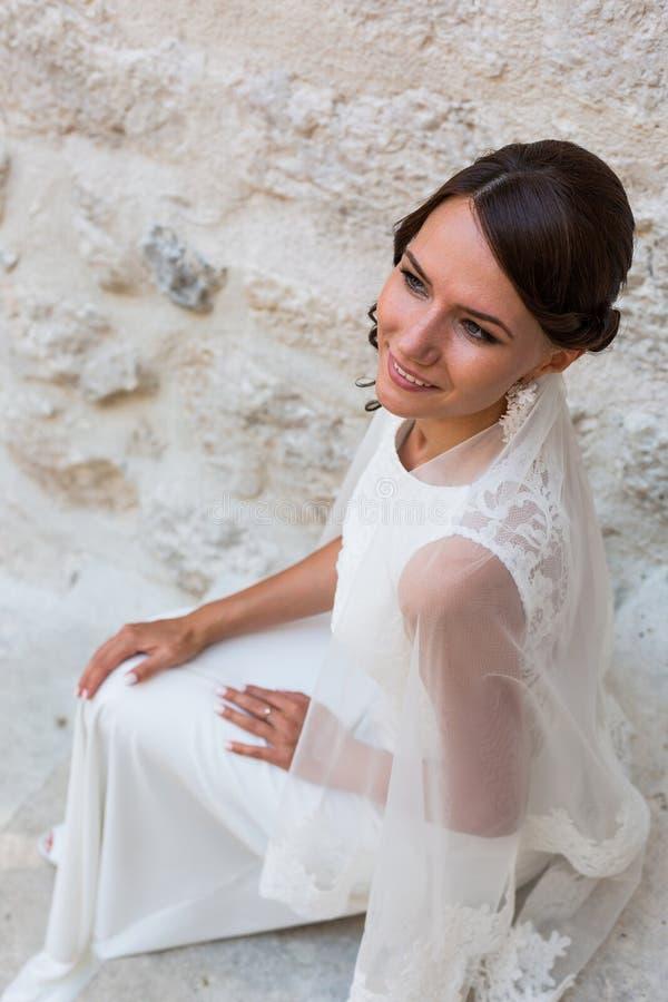 Красивая невеста outdoors представляя на шагах стоковое фото rf