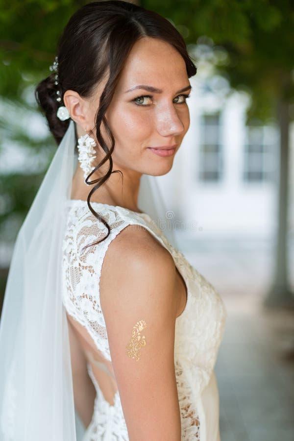 Красивая невеста outdoors представляя под сенью стоковое фото rf