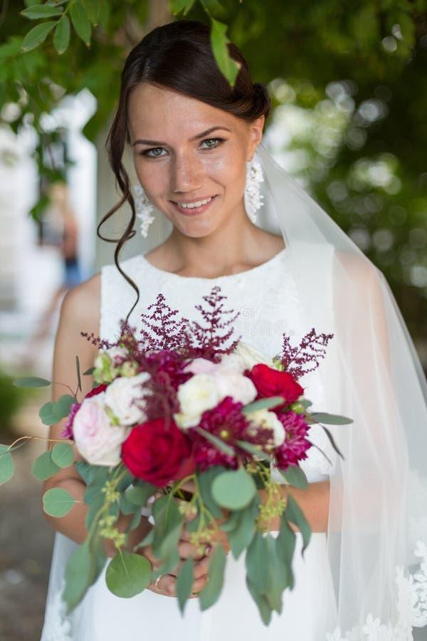 Красивая невеста outdoors с букетом стоковое фото