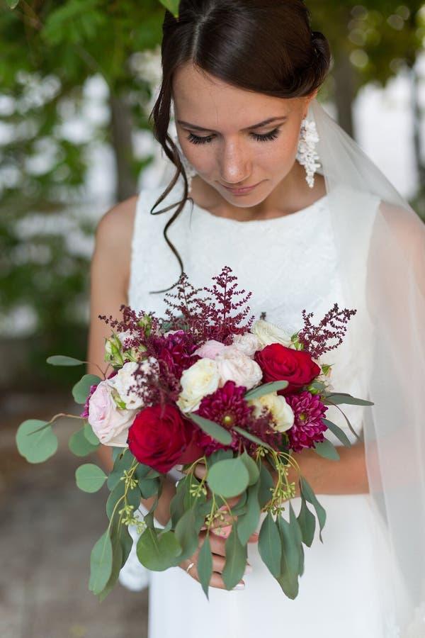 Красивая невеста outdoors с букетом стоковое изображение