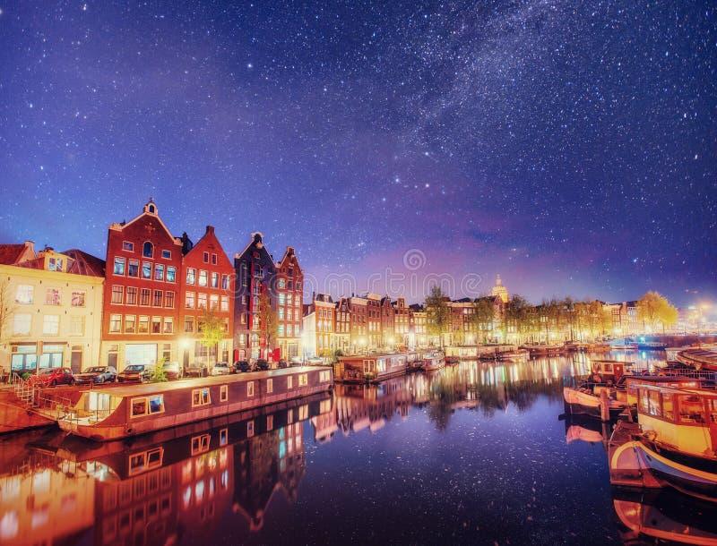 Красивая ноча в Амстердаме Освещение ночи зданий и шлюпок около воды в канале стоковое фото