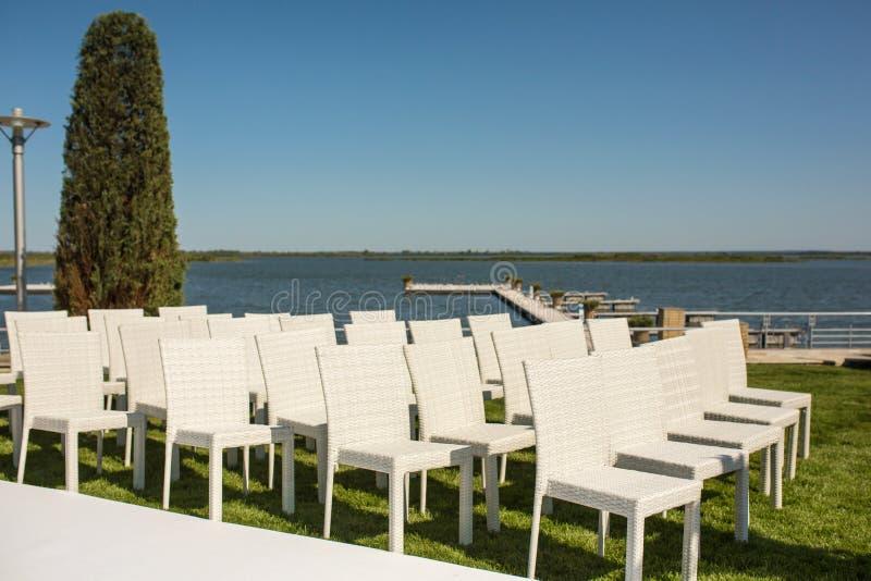 Красивая общительная установка свадьбы Романтичная свадебная церемония, свадьба на открытом воздухе на взгляде воды лужайки Оформ стоковые фото