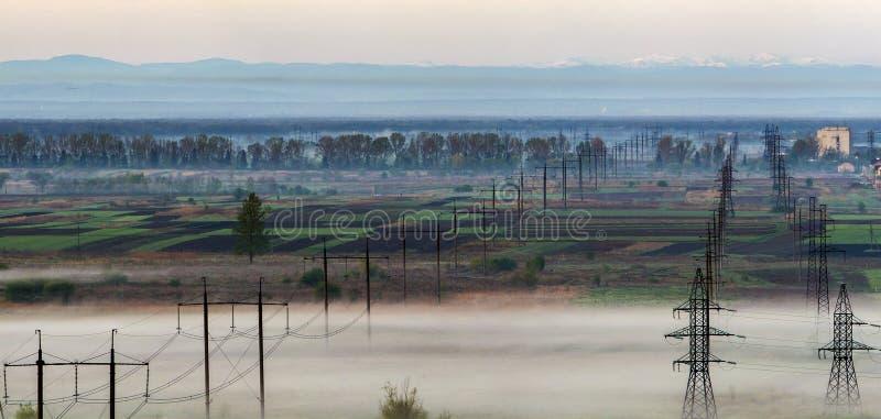 Красивая панорама длинной электрической высоковольтной линии электропередач гребет стоковая фотография rf