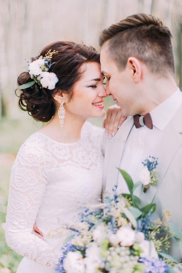 Красивая пара свадьбы с bridal букетом весны цветет в руках на зеленом парке стоковая фотография