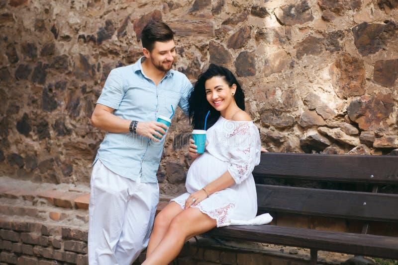 Красивая пара сидит в романтичном месте, усмехается и целуется, выпивающ теплый чай Беременная жена и ее супруг, каменная стена стоковая фотография