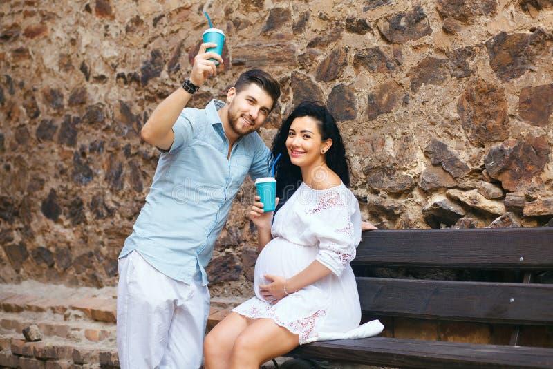 Красивая пара сидит в романтичном месте, усмехается и целуется, выпивающ теплый чай Беременная жена и ее супруг, каменная стена стоковые изображения rf