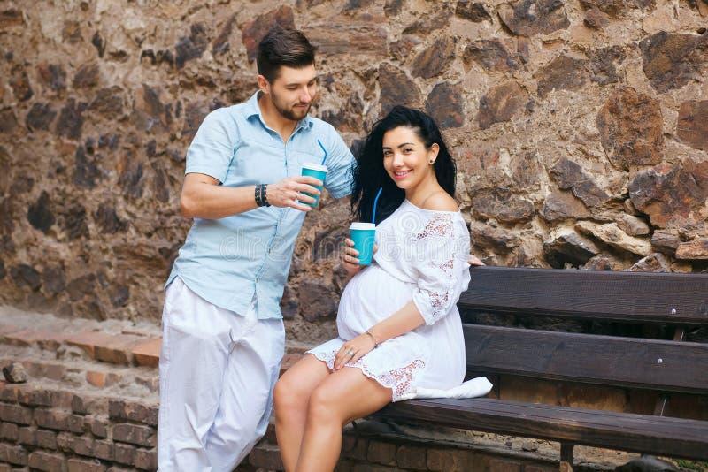 Красивая пара сидит в романтичном месте, усмехается и целуется, выпивающ теплый чай Беременная жена и ее супруг, каменная стена стоковое фото rf