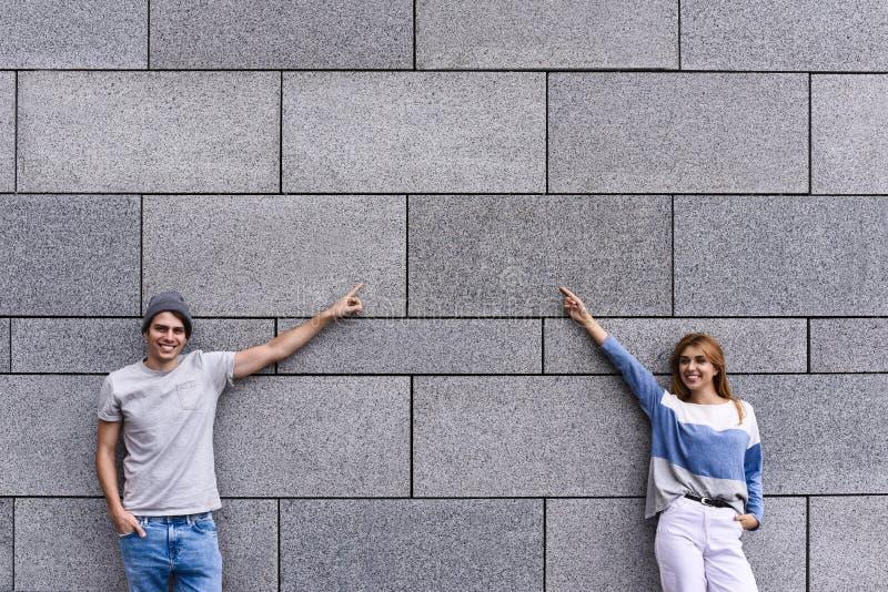 Красивая пара указывает прочь и усмехаться, стоя против серой стены стоковое изображение rf
