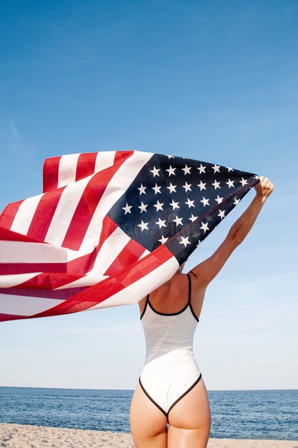 Красивая патриотическая женщина держа американский флаг на пляже День независимости США, 4-ое июля : стоковая фотография