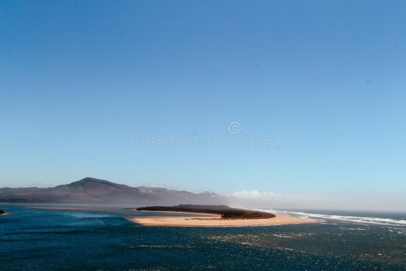 Красивая перспектива моря с маленьким песочным островом в середине и холмах на заднем плане стоковое изображение