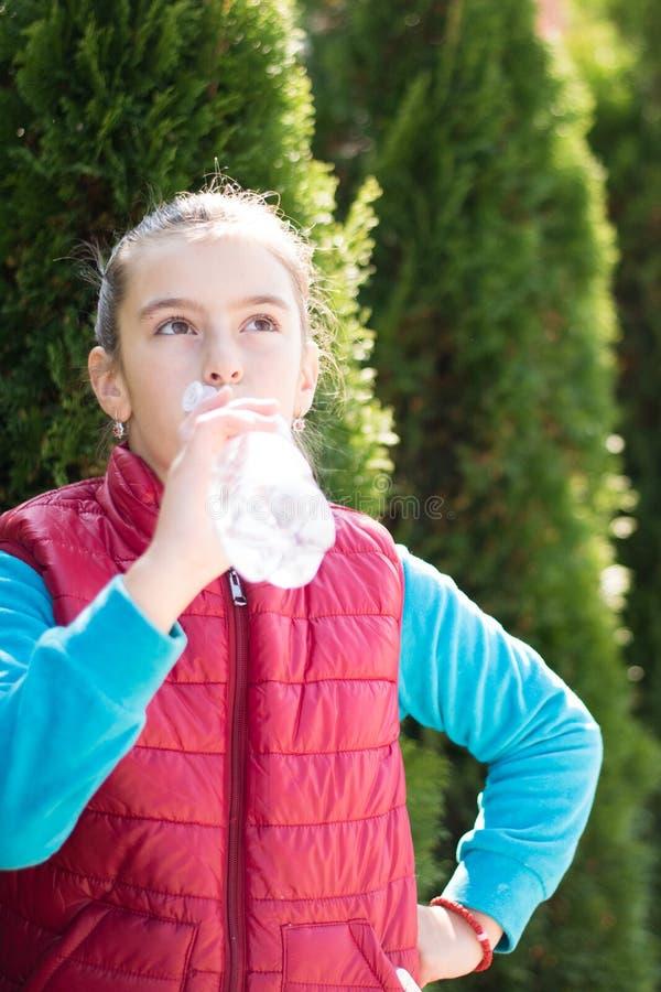 Красивая питьевая вода девушки после jogging в внешнем стоковые фото