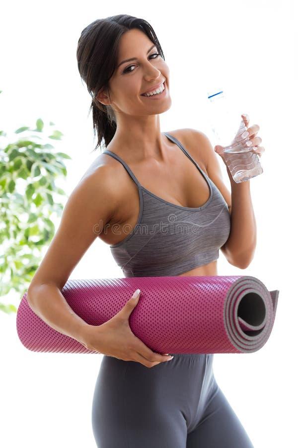 Красивая питьевая вода молодой женщины после разминки дома стоковые изображения