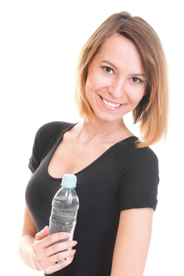 Красивая питьевая вода девушки от голубой изолированной бутылки стоковая фотография