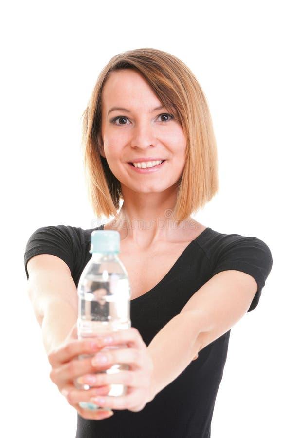 Красивая питьевая вода девушки от голубой изолированной бутылки стоковые изображения