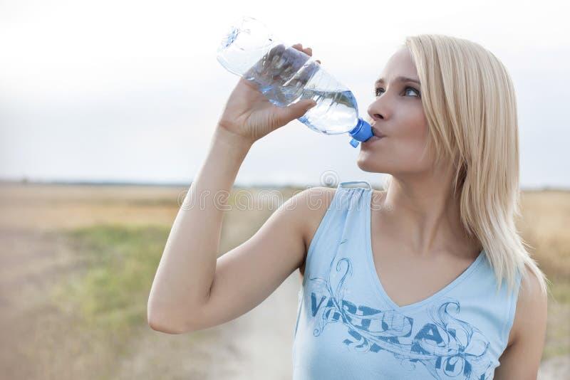 Красивая питьевая вода женщины от бутылки пока стоящ на поле стоковые изображения