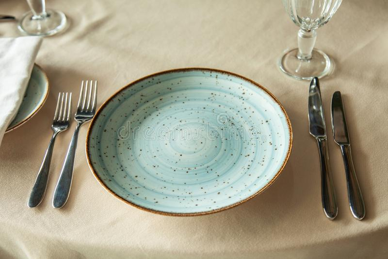 Красивая плита на таблице с вилками и ножами стоковое фото