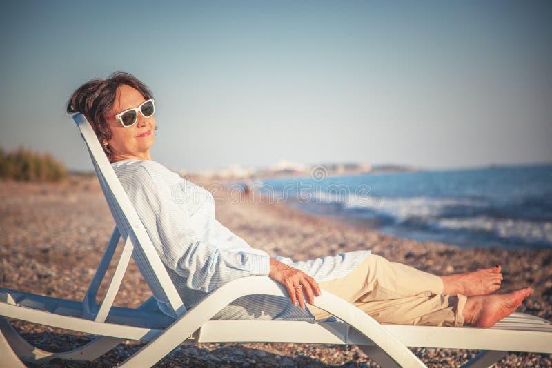 Красивая пожилая женщина сидя в deckchair на пляже и стоковая фотография