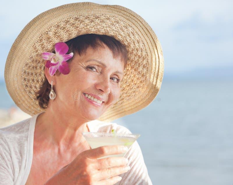Красивая пожилая женщина в шляпе с коктеилем в руке Лето стоковое изображение