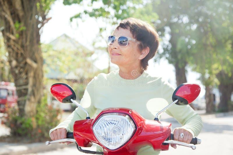 Красивая пожилая женщина на мотоцилк стоковая фотография