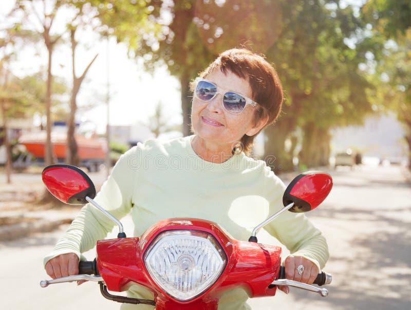 Красивая пожилая женщина на мотоцилк стоковые изображения