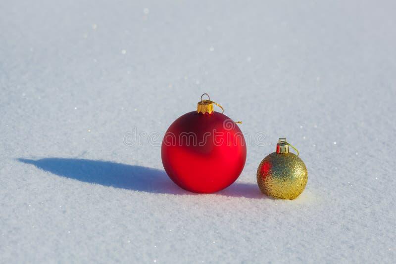 Красивая предпосылка золотых и красных шариков рождества на снеге стоковые изображения
