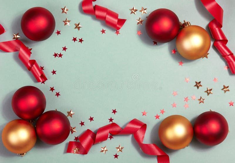 Красивая предпосылка рождества с сияющими красными шариками, звездами яркого блеска и лентой в ярком цвете Взгляд сверху с космос стоковое фото