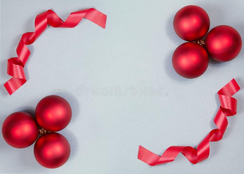 Красивая предпосылка рождества с сияющими красными шариками и лента в ярком цвете Взгляд сверху с космосом экземпляра стоковая фотография