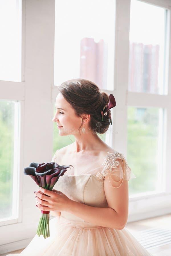 Красивая прелестно невеста в роскошном платье смотря вверх Портрет счастливой невесты сидя в платье свадьбы в студии Молодое attr стоковая фотография