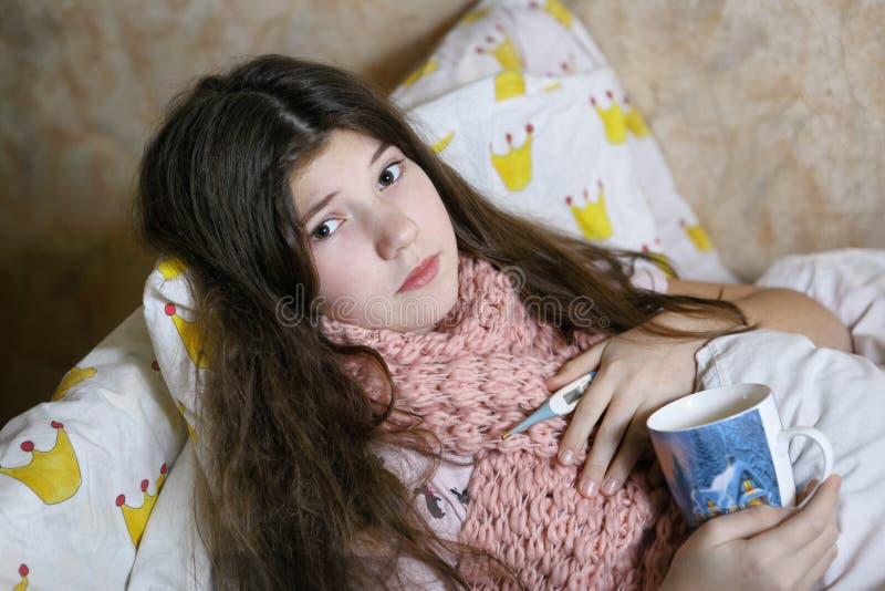 Красивая предназначенная для подростков девушка с длинным больным темных волос в кровати стоковые фото