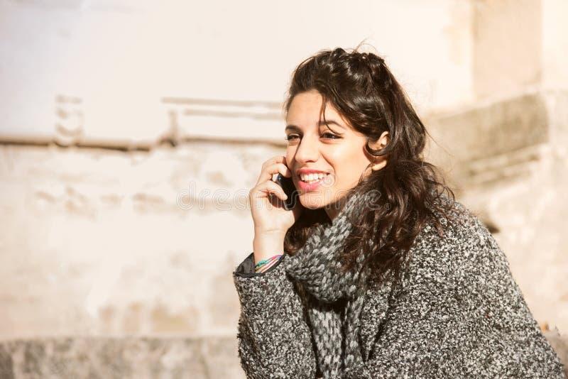 Красивая предназначенная для подростков девушка усмехаясь и говоря на телефоне стоковое фото rf