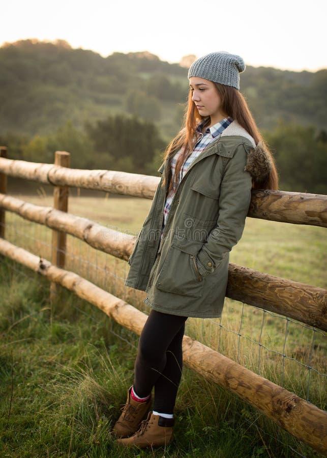 Красивая предназначенная для подростков склонность девушки против загородки фермы стоковое изображение