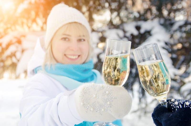 Красивая привлекательная блондинка clinks стекло шампанского в ее руках празднует Новый Год стоковое изображение