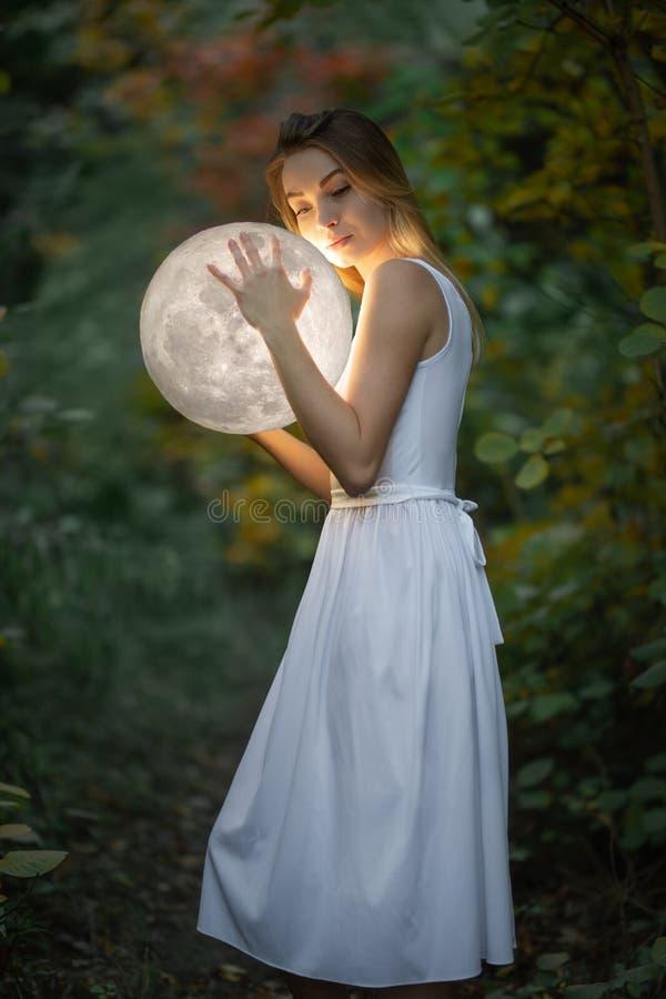 Красивая привлекательная девушка в белом платье в лесе осени, обнимает луну, тайну, загадочный лес, художественный стоковые фотографии rf