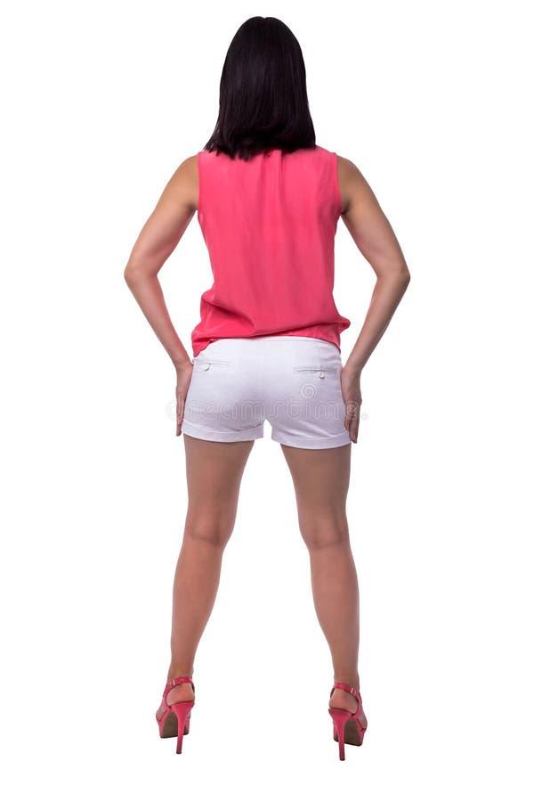 Красивая, привлекательная молодая женщина в блузке и короткие шорты с элегантной диаграммой, батокс, ишак, стоя ОН назад стоковые фотографии rf