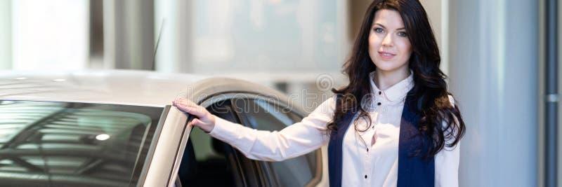 Красивая продавщица possing около нового автомобиля в центре дилерских полномочий стоковое фото