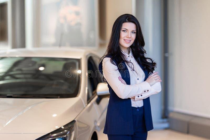 Красивая продавщица possing около нового автомобиля в центре дилерских полномочий стоковые фото