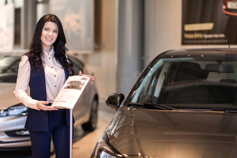 Красивая продавщица possing около нового автомобиля в центре дилерских полномочий стоковое изображение