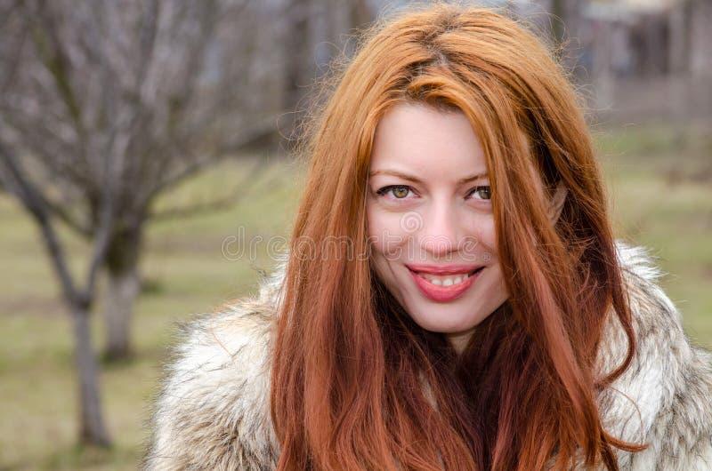 Красивая прочитанная с волосами девушка в меховой шыбе снаружи стоковые фото
