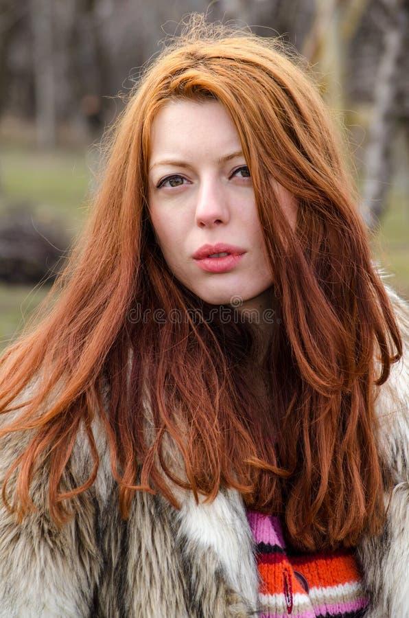 Красивая прочитанная с волосами девушка в меховой шыбе снаружи стоковое фото rf