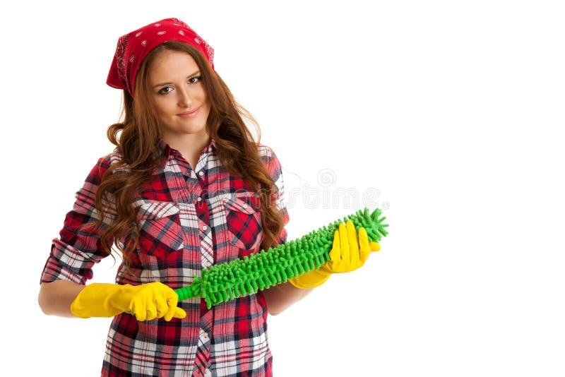 Красивая пыль чистки молодой женщины в checkered изолированной рубашке стоковые фото