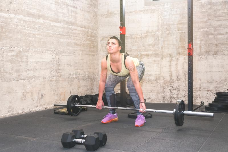 Красивая разминка подъема молодой и привлекательной девушки мертвая в спортзале с малыми весами штанги как червь вверх для тренир стоковое фото rf