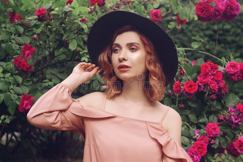 Красивая романтичная молодая женщина на предпосылке розовый естественный представлять цветков Флюиды лета Духи, концепция космети стоковые изображения