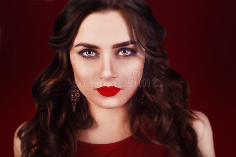 Красивая роскошная женщина с ювелирными изделиями, серьгами Красота и аксессуары Сексуальная девушка брюнет с большими красными г стоковое изображение