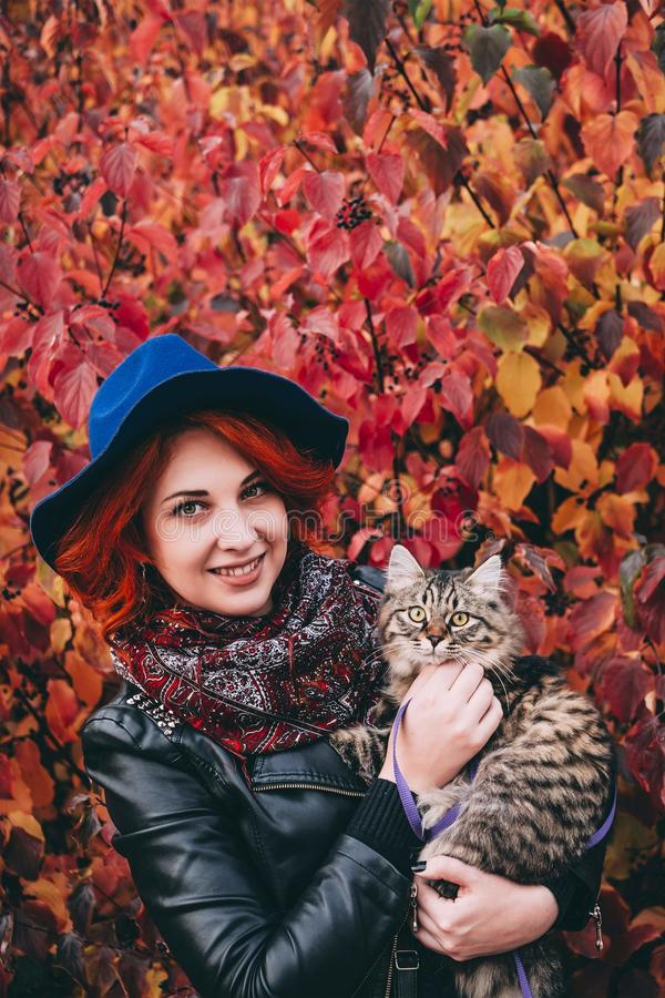 Красивая рыжеволосая женщина в голубой шляпе и кожаной куртке идя с котом в парке красного цвета осени стоковая фотография