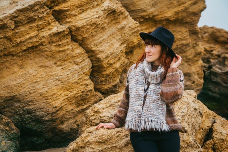 Красивая рыжеволосая женщина в шляпе и положение шарфа на предпосылке утесов Туризм, остатки, образ жизни Космос для стоковое изображение