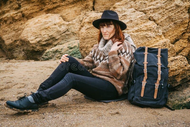 Красивая рыжеволосая женщина в шляпе и шарфе с рюкзаком сидит на побережье на предпосылке утесов стоковое изображение rf