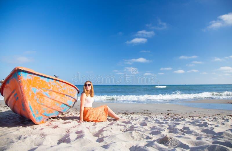 Красивая рыжеволосая маленькая девочка в солнечных очках и юбке ослабляя на пляже около оранжевой шлюпки стоковая фотография rf