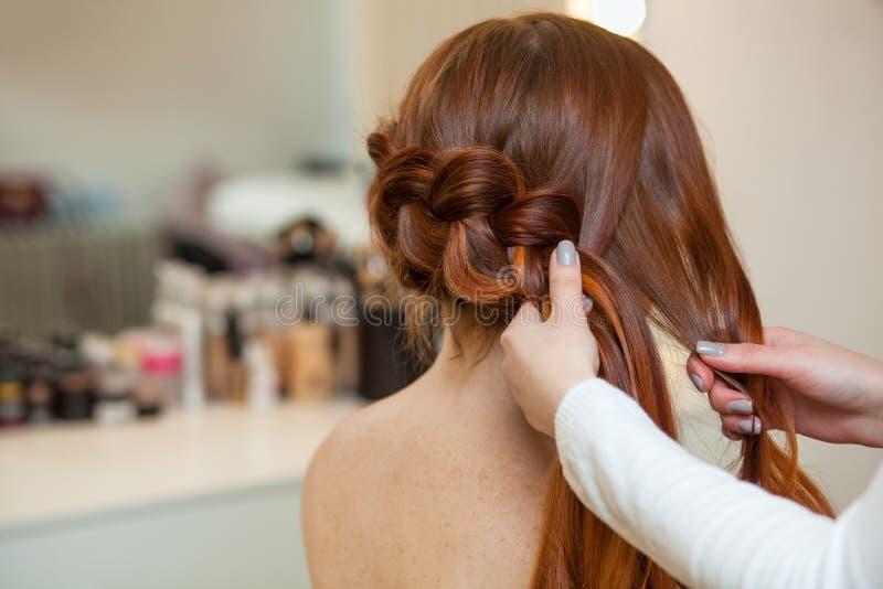 Красивая, рыжеволосая девушка с длинными волосами, парикмахер соткет французскую оплетку, в салоне красоты стоковое фото